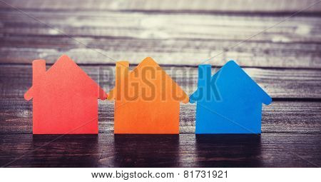 Three Paper Houses On Wooden Table.