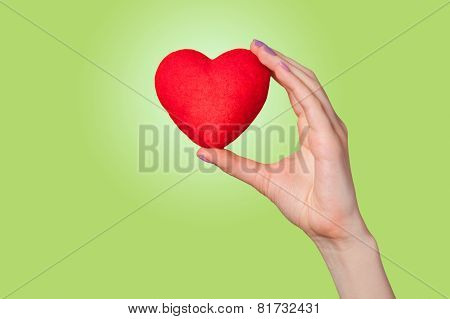 Hand Holding Shape Heart On Green Background.