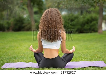Pretty woman sitting back doing yoga meditation