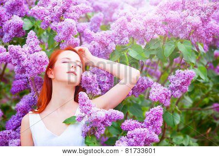 Redhead Girl Near Lilac Tree In The Garden.