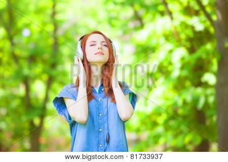 Redhead Women With Headphones In The Park.