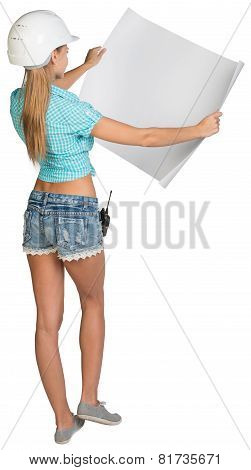 Woman in hard hat showing blank sheet of drawing paper. Rear view