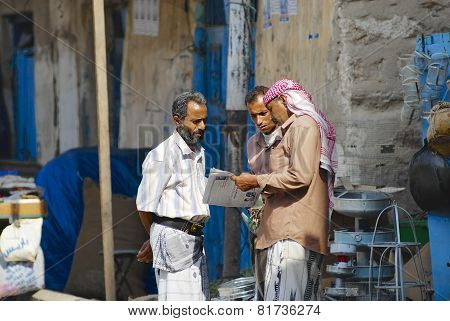Men read newspaper at the street in Sanaa, Yemen.