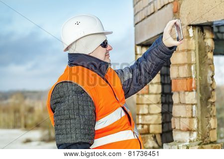 Engineer with tablet PC take a picture near unfinished building