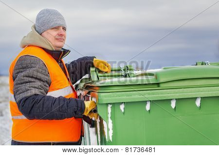 Worker near the garbage containers in winter