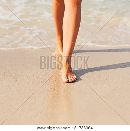 Close-up View Of Women's Legs On The Beach.