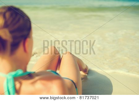 Young Woman Sunbathing Near The Sea.