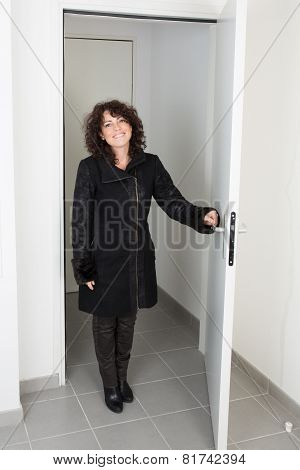 Woman In A Coat Walks Into A Room Through The Door
