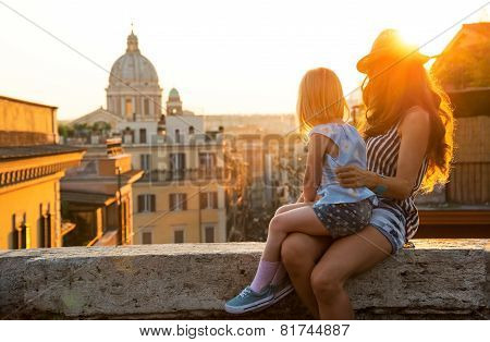 Mother And Baby Girl Sitting On Street Overlooking Rooftops Of R