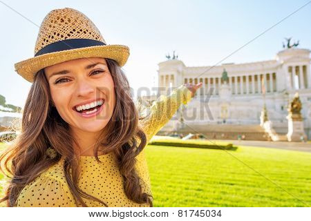 Portrait Of Happy Young Woman Pointing On Piazza Venezia In Rome, Italy