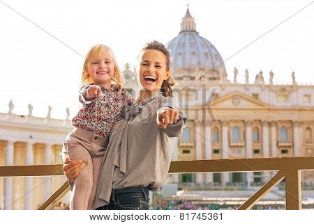Happy Mother And Baby Girl On Piazza San Pietro In Vatican City State Pointing In Camera
