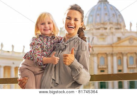 Portrait Of Happy Mother And Baby Girl On Piazza San Pietro In Vatican City State Showing Thumbs Up