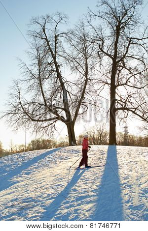 Girl enjoying cross-country skiing running up in sunny day