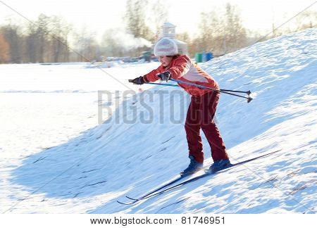 Girl enjoying cross-country skiing down in sunny day