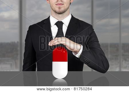 Businessman Holding Protective Hand Above Large Pill