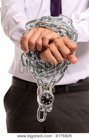 Mãos de empresário restringidas com corrente e cadeado, símbolo de trabalho escravo, isolaram no fundo branco
