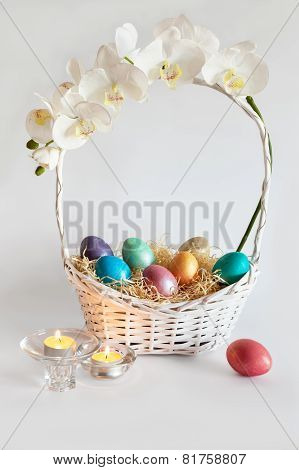 Easter eggs in the basket with flowers and candles