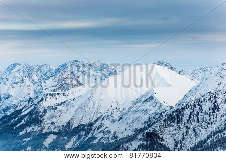 one smooth snowy mountain between rough rocks in austria