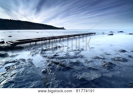 Wooden Pier Or Jetty On A Blue Ocean In The Morning. Long Exposure