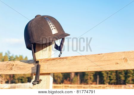Equestrian Helmet Forgotten Hanging On The Wooden Fence.
