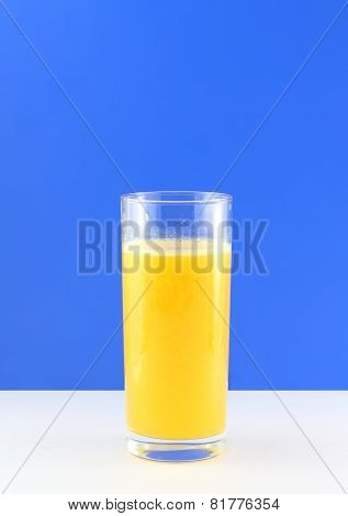 Glass Of Fresh Orange Juic? On  Blue Background.