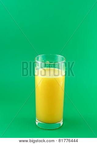 Glass Of Fresh Orange Juice On  Green Background.