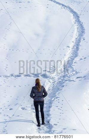 Woman Walking Alone On A Foot Track Into The Snow In Wintertime