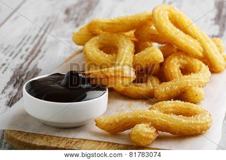 churros with chocolate sweet dessert on a wooden surface