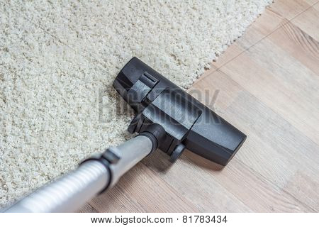Vacuum cleaner being used to vacuum a carpet