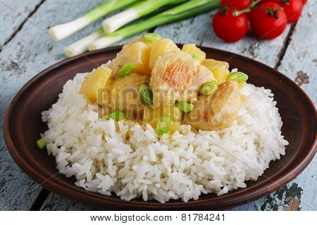 chicken curry with rice salad plate on a wooden surface
