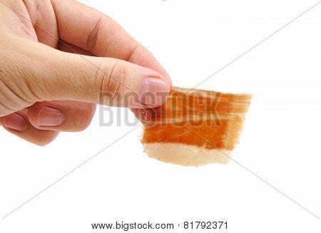 Man holding a hand cut serrano ham slice isolated on white background. Jabugo. Spanish tapa.