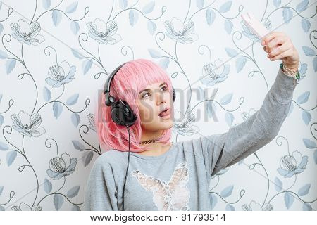 Young hipster woman in pink wig and dj headphones doing selfie against wall