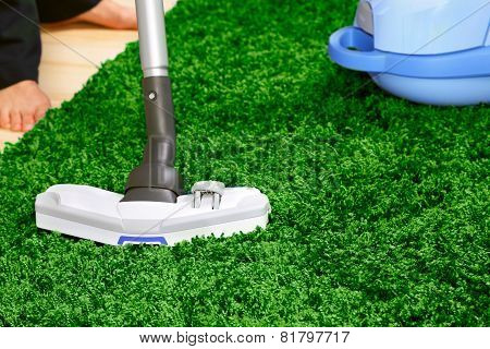 The metal pipe of vacuum cleaner in action -clean a carpet