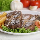 stock photo of pork chop  - Pork chops steaks meat meal with fries and salad on plate - JPG