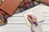 picture of office romance  - Female hand writing something in to notebook - JPG