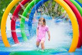 picture of happy day  - Happy little toddler girl running through a fountain having fun with water splashes in a swimming pool enjoying day trip to an aqua amusement park during summer family vacation - JPG