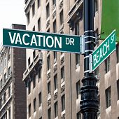 stock photo of sabbatical  - A sign post at the intersection of two streets reading VACATION DR and BEACH ST - JPG