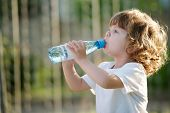 picture of plastic bottle  - little beautiful girl drinking clean water from plastic bottle - JPG