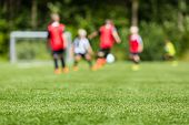 stock photo of foreground  - Picture of kids soccer training match with shallow depth of field. Focus on foreground.