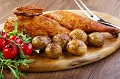 stock photo of baked potato  - half baked chicken with new potatoes on the board - JPG