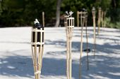 stock photo of tiki  - Decoration tiki oil torches burning outside on the beach