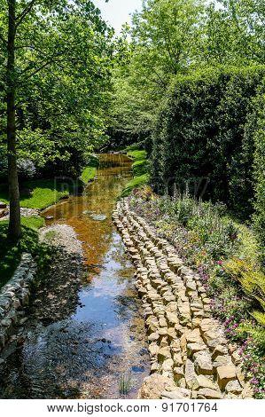 Stone Bank Of Stream Through Garden
