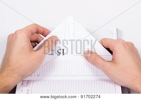 male hands folded sheet of paper from the diary