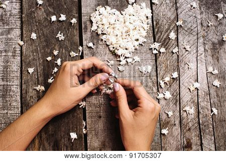 Wedding Ring In Hands And White Heart Of Flowers Background