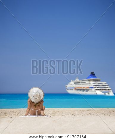 Woman relaxing on the famous Shipwreck Navagio beach in Zakynthos Greece watching a cruiseship passing by