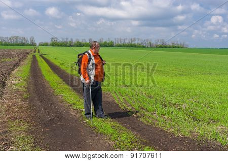 Senior man standing on country road