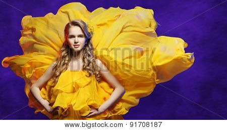 Fashion Model Girl In Yellow Dress, Young Woman Posing In Flowing Fabric, Blue Background
