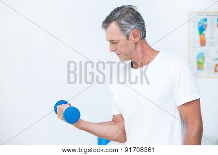 Patient lifting dumbbell in medical office