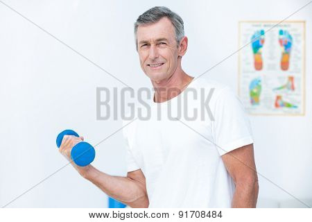 Patient looking at camera and lifting dumbbell in medical office