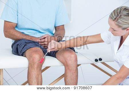 Doctor checking reflexes of the knee of her patient in medical office